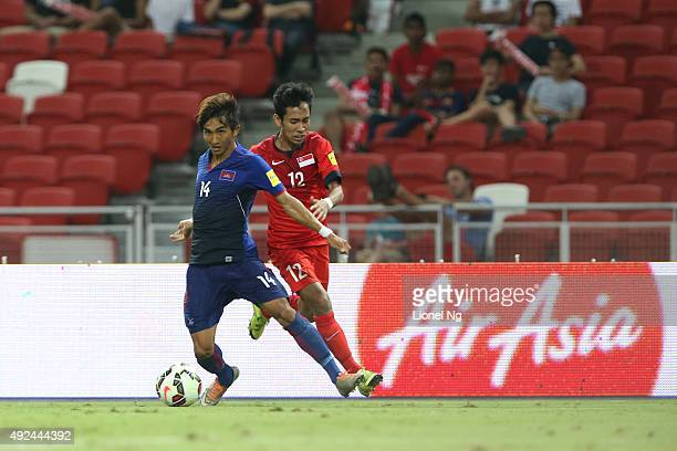 Keo Sokpheng of Cambodia keeps the ball away from Muhammad Nazrul Bin Ahmad Nazari of Singapore during the FIFA 2018 World Cup Qualifier match...