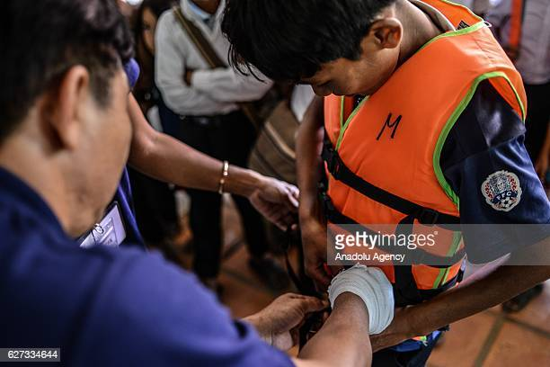 Keo Sopheap and Chan Sovanna from Safety When It Matters Cambodia help a student put on a life jacket during a safety and drowning prevention class...