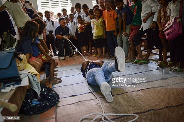 Keo Sopheap from Safety When It Matters Cambodia pulls colleague Chan Sovanna with a rope demonstrating how to rescue someone during a safety and...