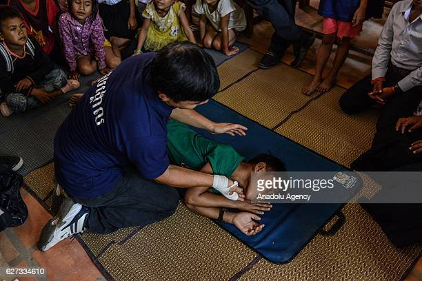 Keo Sopheap from Safety When It Matters Cambodia puts a student in the recovery position during a safety and drowning prevention class on Monday...
