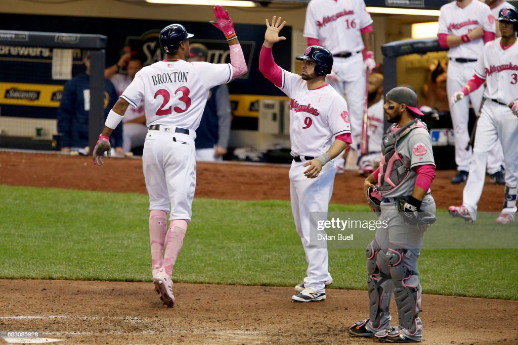 Keon Broxton #23 and Manny Pina #9 of the Milwaukee Brewers celebrate after Broxton hit a home run in the sixth inning against the New York Mets at Miller Park on May 14, 2017 in Milwaukee, Wisconsin. Players are wearing pink to celebrate Mother's Day weekend and support breast cancer awareness.