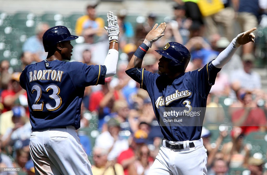 Keon Broxton #23 and Orlando Arcia #3 of the Milwaukee Brewers celebrate after scoring runs in the first inning against the Cincinnati Reds at Miller Park on August 14, 2016 in Milwaukee, Wisconsin.