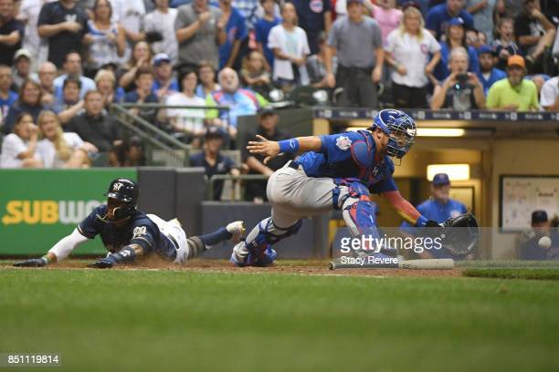 Keon Broxton of the Milwaukee Brewers beats a tag at home plate by Willson Contreras of the Chicago Cubs during the seventh inning of a game at...
