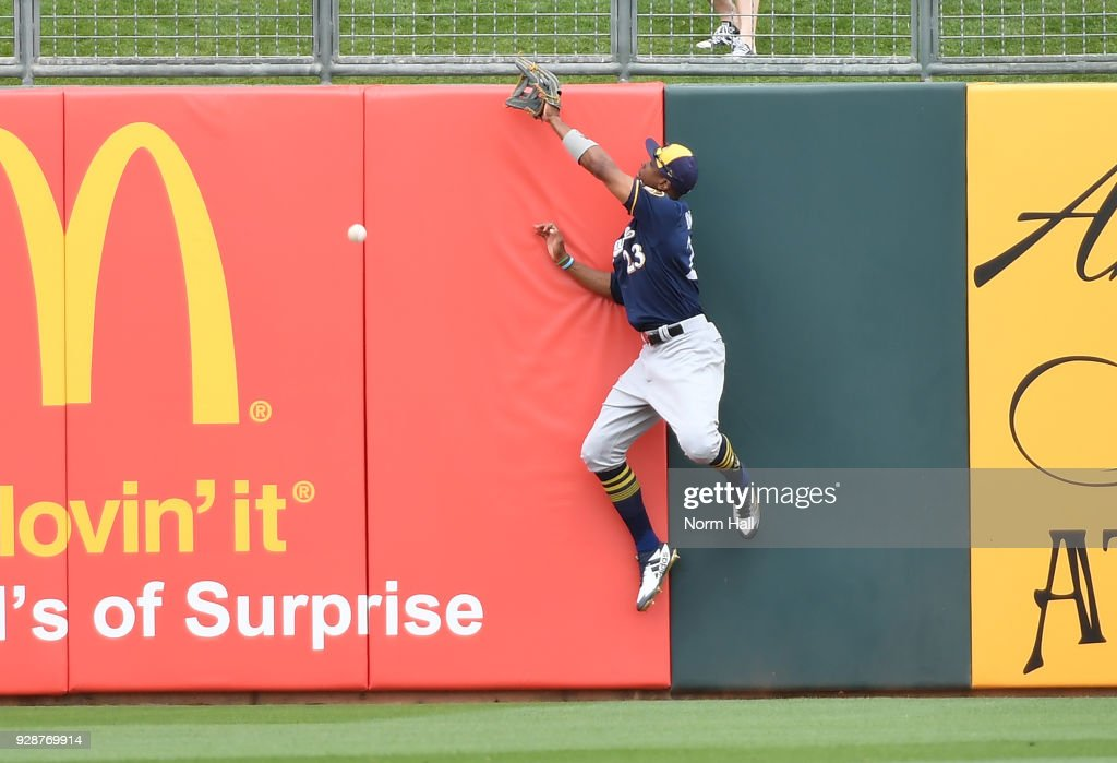 Keon Broxton #23 of the Milwaukee Brewers crashes into the outfield wall attempting to make a leaping catch on a hit by Tyler Collins #7 of the Kansas City Royals during the second inning of a spring training game at Surprise Stadium on March 7, 2018 in Surprise, Arizona. Collins ended up with a triple.
