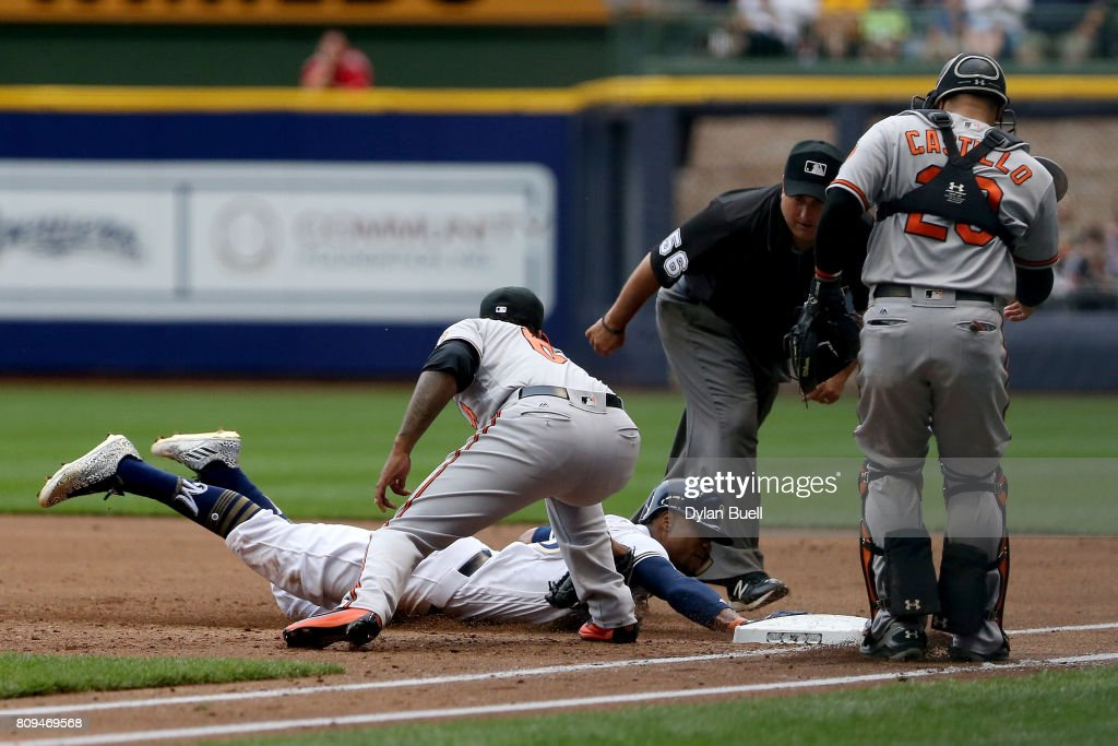 Keon Broxton #23 of the Milwaukee Brewers dives into first base past the tag attempt of Jayson Aquino #64 of the Baltimore Orioles during a run down in the second inning at Miller Park on July 5, 2017 in Milwaukee, Wisconsin.