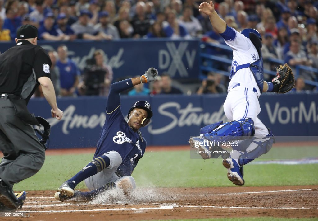 Keon Broxton #23 of the Milwaukee Brewers slides across home plate to score a run in the third inning during MLB game action as Russell Martin #55 of the Toronto Blue Jays jumps for an errant throw at Rogers Centre on April 11, 2017 in Toronto, Canada.