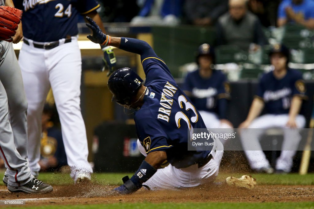 Keon Broxton #23 of the Milwaukee Brewers slides into home plate to score a run on a wild pitch in the fifth inning against the Atlanta Braves at Miller Park on April 29, 2017 in Milwaukee, Wisconsin.