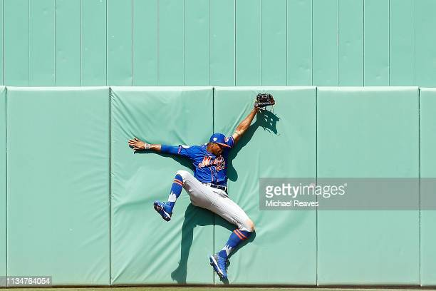 Keon Broxton of the New York Mets crashes into the wall as he attempts to catch a flyball against the Boston Red Sox in the sixth inning of the...