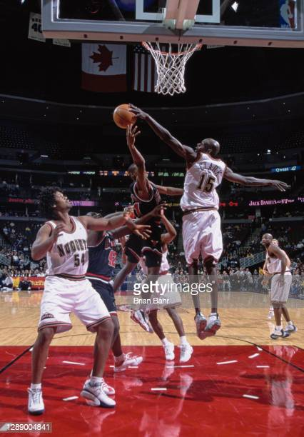 Keon Clark, Center and Power Forward for the Denver Nuggets blocks the drive to the basket by A.J. Guyton of the Chicago Bulls during the NBA Midwest...