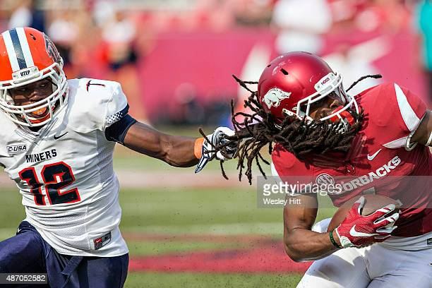 Keon Hatcher of the Arkansas Razorbacks is tackled by his hair by Adrian Hynson of the UTEP Miners at Razorback Stadium on September 5, 2015 in...