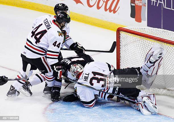 Keoni Texeira of the Portland Winterhawks checks James Malm of the Vancouver Giants into Winterhawks goaltender Adin Hill during the first period of...