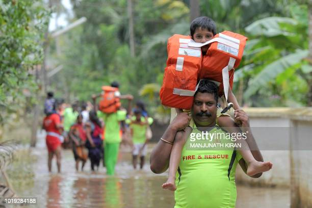 TOPSHOT Kerala and Tamil Nadu Fire Force personnel carry children on their shoulders through flood waters during a rescue operation in Annamanada...