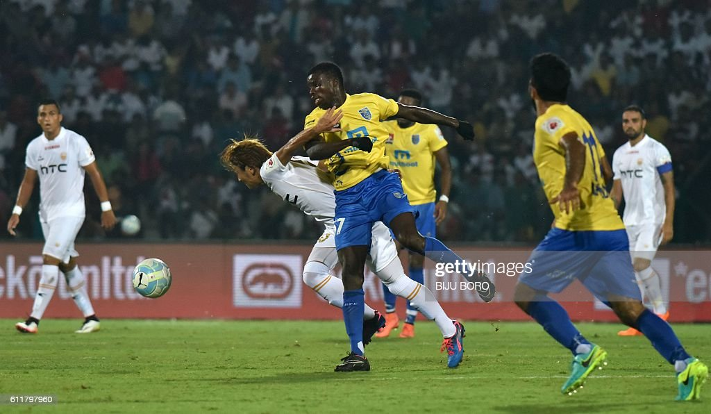 Kerala Blasters FC's midfielder Didier Boris Kadio(C/R) and Northeast United FC's midfielder Katsumi Yusa (C/L) fight for the ball during the Indian Super League (ISL) football match between Northeast United FC and Kerala Blasters FC at The Indira Gandhi Athletic Stadium in Guwahati on October 1, 2016. USE-- / AFP / Biju BORO