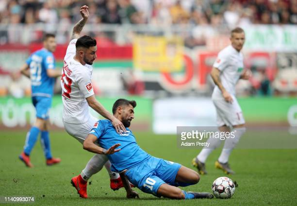 Kerem Demirbay of 1899 Hoffenheim is brought down by Marco Richter of Augsburg during the Bundesliga match between FC Augsburg and TSG 1899...