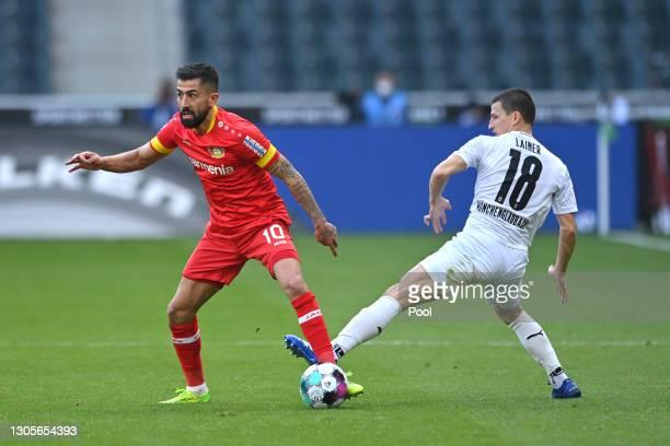 Kerem Demirbay of Bayer 04 Leverkusen is challenged by Laszlo Benes of Borussia Moenchengladbach during the Bundesliga match between Borussia...