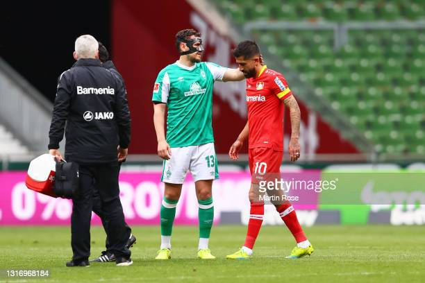 Kerem Demirbay of Bayer Leverkusen is consoled by Milos Veljkovic of Werder Bremen as he walks off the pitch after an injury during the Bundesliga...