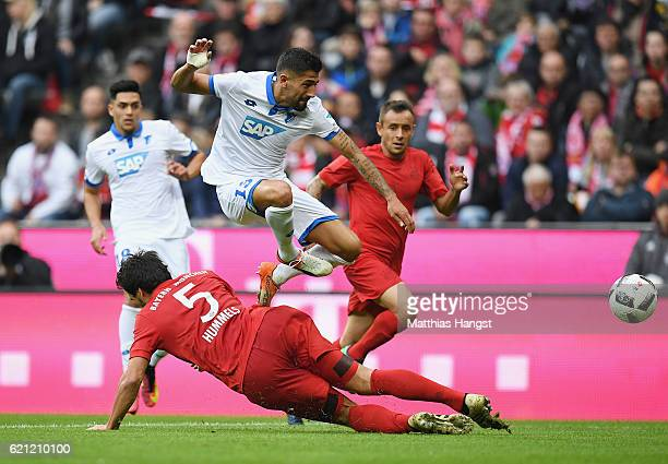 Kerem Demirbay of Hoffenheim is challenged by Mats Hummels of Muenchen during the Bundesliga match between Bayern Muenchen and TSG 1899 Hoffenheim at...
