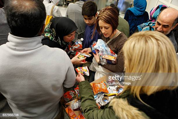 Keri Puckett hands out snacks and water to protesters gathered to denounce President Donald Trump's executive order that bans certain immigration at...
