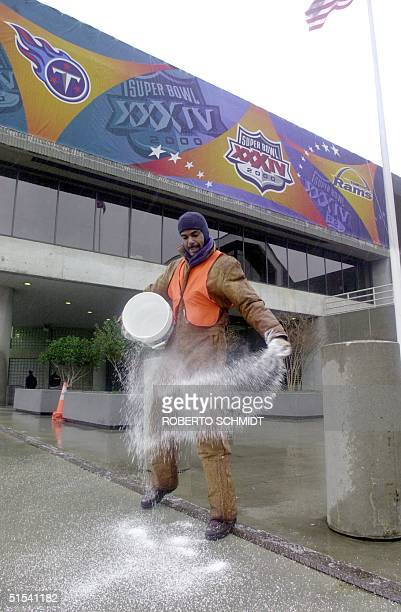 Kermin Tuner a groundskeeper for the Georgia World Conference Center throws salt on the sidewalk in front of the NFL Experience entrance in an effort...