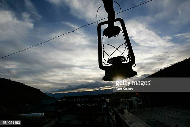 – – Kerosene lantern silhouetted against evening sky hangs outside Cerro Gordo museum a relict of days gone by The former rip–roaring 1870s silver...