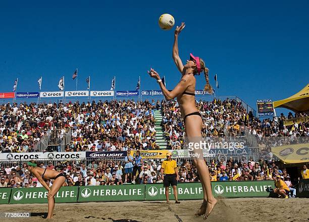 Kerri Walsh serves while partner Misty May-Treanor watches during the women's finals against Elaine Youngs and Nicole Branaugh in the AVP San...