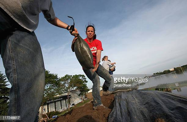 Kerri Zablotney helps to build a levee around her family's implement business on June 24 2011 in Minot North Dakota Residents of Minot are scrambling...
