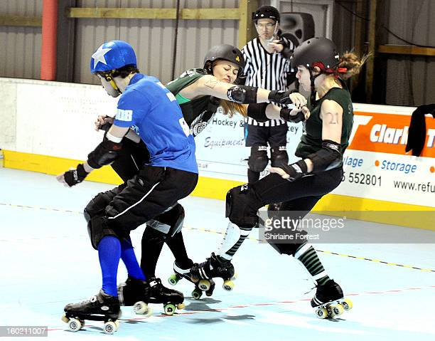 Kerried Alive and Sirenide of Manchester Roller Derby block jammer Beat Monkey of Sheffield Steel Roller Derby during the first UK CoEd Roller Derby...