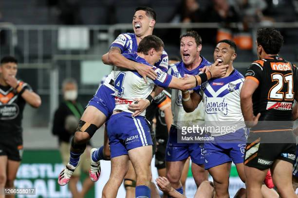 Kerrod Holland of the Bulldogs celebrates with team mates after scoring a try during the round 14 NRL match between the Wests Tigers and the...