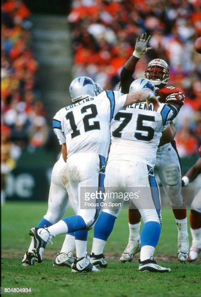 Kerry Collins of the Carolina Panthers gets his pass off under pressure from Dana Stubblefield of the San Francisco 49ers during an NFL football game...