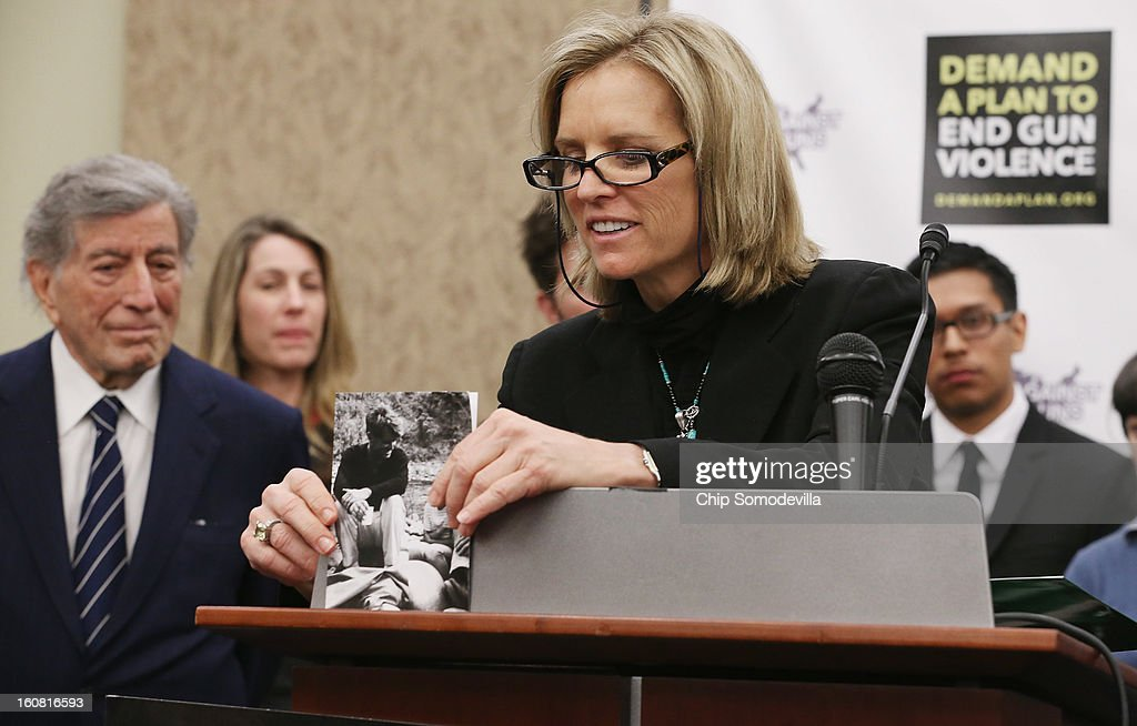 Kerry Kenendy, daughter of Robert F. Kennedy, places a photograph of her and her father on the podium before speaking during a press conference hosted by the Mayors Against Illegal Guns and the Law Center to Prevent Gun Violence with (L-R) singer Tony Bennett, LCPGV Executive Director Robyn Thomas, and student Luis Melchor at the U.S. Capitol February 6, 2013 in Washington, DC. The artists, activists and politicians called for manditory background check on all gun purchases among other restrictions.