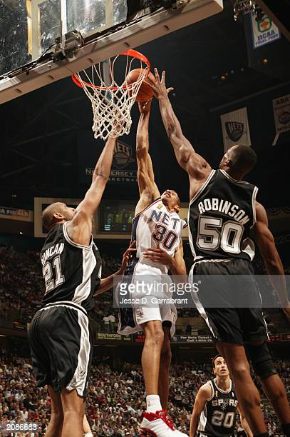 Kerry Kittles of the New Jersey Nets goes to the basket against Tim Duncan and David Robinson of the San Antonio Spurs in Game three of the 2003 NBA...
