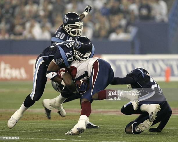 Kerry Watkins of the Montreal Alouettes is tackled by Orlondo Steinauer of the Toronto Argonauts in Canadian Football League action at Rogers Centre...