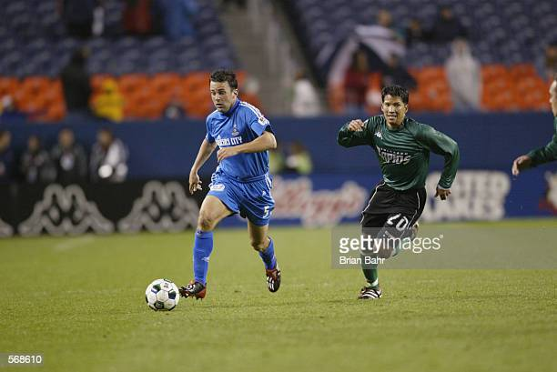Kerry Zavagnin of the Kansas City Wizards dribbles against the defense of Mark Chung of the Colorado Rapids during the MLS match at Mile High Stadium...