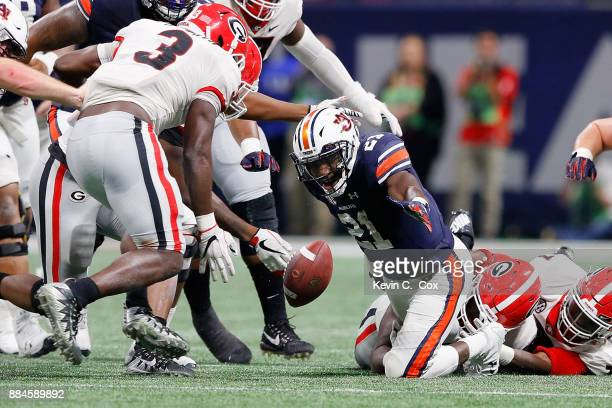 Kerryon Johnson of the Auburn Tigers fumbles when tackled by Lorenzo Carter and Julian Rochester of the Georgia Bulldogs during the second half in...