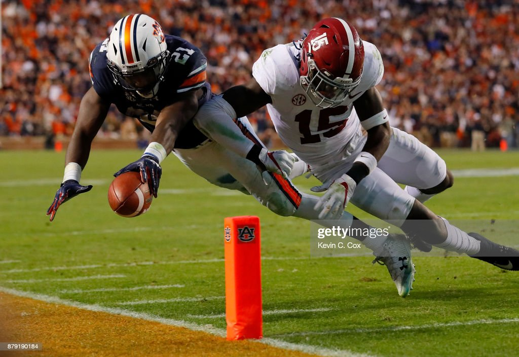 Kerryon Johnson #21 of the Auburn Tigers is hit by Ronnie Harrison #15 of the Alabama Crimson Tide diving towards the endzone during the third quarter of their game at Jordan Hare Stadium on November 25, 2017 in Auburn, Alabama.