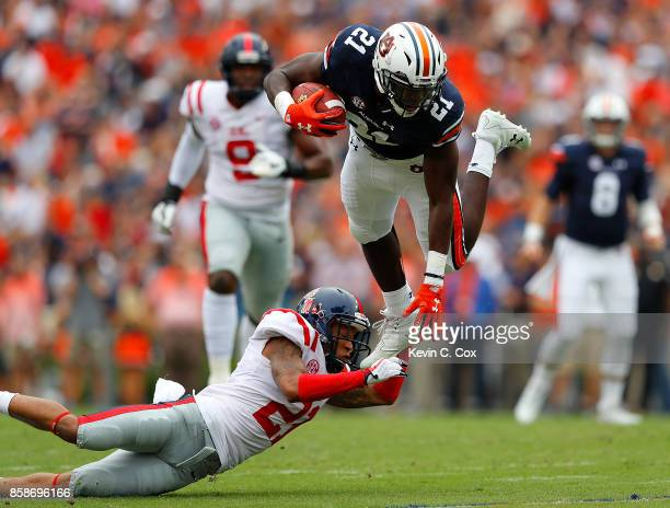 Kerryon Johnson of the Auburn Tigers is tripped up as he leaps over Javien Hamilton of the Mississippi Rebels at Jordan Hare Stadium on October 7...