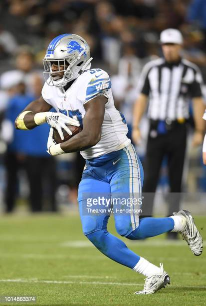 Kerryon Johnson of the Detroit Lions carries the ball against the Oakland Raiders during the fourth quarter of an NFL preseason football game at...