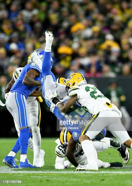 Kerryon Johnson of the Detroit Lions is tackled by Jaire Alexander of the Green Bay Packers at Lambeau Field on October 14 2019 in Green Bay Wisconsin