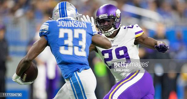 Kerryon Johnson of the Detroit Lions runes for a short gain as Xavier Rhodes of the Minnesota Vikings gets ready to make the top during the first...