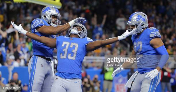 Kerryon Johnson of the Detroit Lions scores a touchdown and celebrates with teammates Jason Cabinda and Logan Thomas during the second quarter of the...