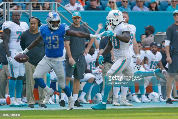 Kerryon Johnson of the Detroit Lions stiff arms Reshad Jones of the Miami Dolphins as he runs with the ball during an NFL game on October 21 2018 at...