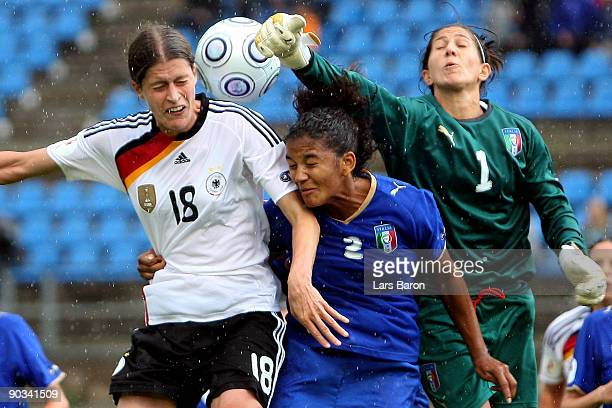Kerstin Garefrekes goes up for a header with Sara Gama and goalkeeper Anna Maria Picarelli of Italy during the UEFA Women's Euro 2009 quarter final...