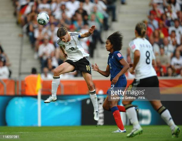 Kerstin Garefrekes of Germany rises to score the opening goal under pressure from Wendie Renard of France during the FIFA Women's World Cup 2011...