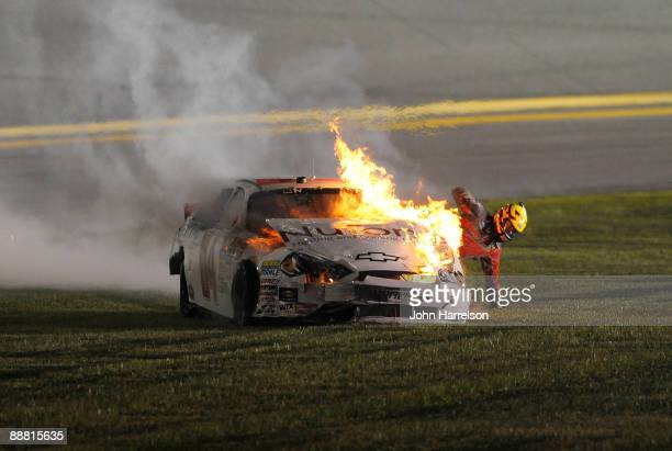 Kertus Davis, driver of the NuTone Heating & Cooling Products Chevrolet, climbs out of his car after it catches fire prior to a crash on track during...