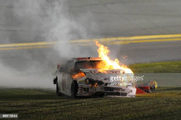 Kertus Davis driver of the NuTone Heating Cooling Products Chevrolet falls to the ground after he climbs out of his car after it catches fire prior...