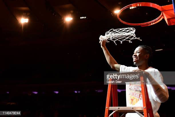 Kerwin Roach II of the Texas Longhorns cuts the net after the Texas Longhorns win 8166 over the Lipscomb Bisons during the NIT Championship game at...