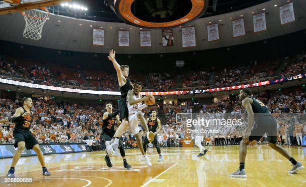 Kerwin Roach II of the Texas Longhorns leaps in the lane to make the winning score against Mitchell Solomon of the Oklahoma State Cowboys at the...