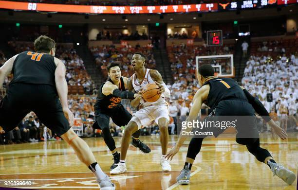 Kerwin Roach II of the Texas Longhorns moves with the ball against Lindy Waters III Mitchell Solomon and Kendall Smith of the Oklahoma State Cowboys...