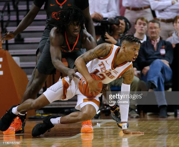 Kerwin Roach II of the Texas Longhorns moves with the ball in front of Isaac Likekele of the Oklahoma State Cowboys at The Frank Erwin Center on...