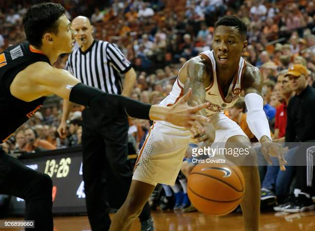 Kerwin Roach II of the Texas Longhorns passes the ball around Lindy Waters III of the Oklahoma State Cowboys at the Frank Erwin Center on February 24...